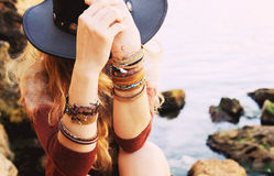 Female hands with boho chic bracelets holding black hat. Fashion photo against sea and rock stones, outdoor Stock Photos