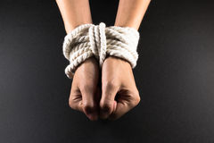 Female Hands Bound in Bondage with Rope. White female hands in bondage tied up with white rope stock photography