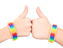 Female hands with a bracelet patterned as the rainbow flag showing thumbs up. isolated on white background.  Stock Photography