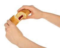 Female hands breaking a croissant with marmalade Stock Photo
