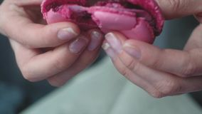Female hands breaking open a pink macaroon. Female breaking open a pink macaroon. close up stock footage