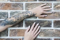 Female hands on a brick wall. Female hands with tattoos and manicure on an old brick wall stock images