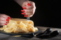 Female hands with bright beautiful manicure break away pieces of hard cheese like parmesan by means a special knife. Female hands with bright beautiful manicure Stock Photos