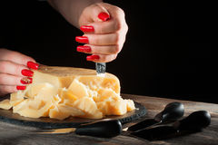 Female hands with bright beautiful manicure break away pieces of hard cheese like parmesan by means a special knife. Female hands with bright beautiful manicure Royalty Free Stock Photos