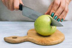 Female hands with a bright manicure cut green apple with a kitch Royalty Free Stock Photos