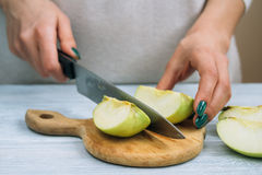 Female hands with a bright manicure cut with a kitchen knife gre Stock Photo