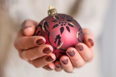Female hands with brown nail polish manicure holding red Christmas ball. Beautiful woman hands with brown nail polish manicure holding red Christmas ball royalty free stock image
