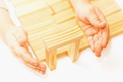 Female hands building small wooden house from wodden block for kids on white background. Household concept. stock image