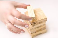Female hands building small wooden tower house from wodden block for kids on white background. Business household concept. stock photo