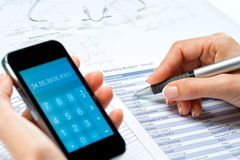 Female hands calculating budget with smart phone. Royalty Free Stock Photo
