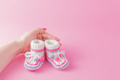 Female hands carefully holing baby shoes Stock Photo