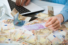 Female hands with cash near laptop Royalty Free Stock Image