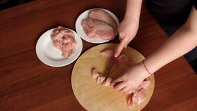 Female hands chef cutting raw chicken meat breast. The crude chicken meat cut on pieces on a wooden board. Female chef cuts raw chicken meat on a round wooden stock video footage