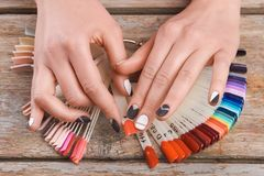 Female hands choose peach cnail color. Woman hands holding color nail polish on old wooden background stock photography