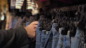 Female hands choosing chinos in the clothing store close-up with changing focus. Shopping stock footage