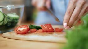 Female hands chopping fresh eco tomato use knife on wooden board. Close up shot on 4k RED camera