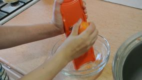 Female hands chopping raw carrots with a trowel. Home kitchen. stock video footage