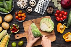 Female hands chopping savoy cabbage on wooden board. Balanced eating. Female hands chopping savoy cabbage on wooden board, kitchen table with vegetables royalty free stock photos
