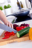 Female hands chopping vegetables on a wooden board Stock Image