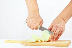 Female hands chops onion on a cutting board Stock Photography