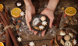 Female hands with christmas decoration. On a rustic wooden table Stock Photography
