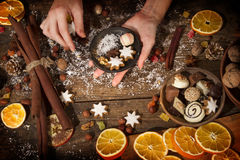 Female hands with christmas decoration. On a rustic wooden table Stock Image
