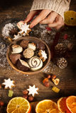 Female hands with christmas decoration. On a rustic wooden table Royalty Free Stock Photography
