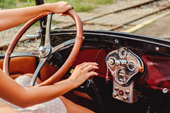 Female hands on classic car wheel and shift Royalty Free Stock Photos