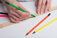 Female hands with classical French manicure draw a pencil by means of a ruler on clean standard sheet. Female hands with beautiful classical French manicure draw Stock Photography