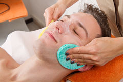 Female hands cleaning man's face  in a spa center Royalty Free Stock Photography