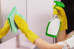 Female hands cleaning mirror with green cloth. Spring clean up. Cleanness in every move. Woman cleans mirror with help of green cloth and special mean of royalty free stock image