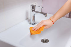 Female hands cleaning tap with orange cloth. Spring clean up Stock Photos