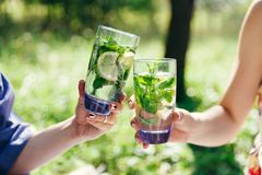Female hands clinking glasses filled water with lemon and green mint leaves. Picnic in the garden. Detox, healthy eating, drinks, diet and people concept stock images