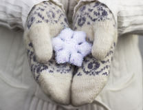 Female hands close up in knitted wore mittens holding white snowflake outdoors. Royalty Free Stock Images