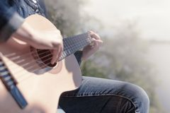 Female hands close up playing guitar on background in blur. Summer Sunny day royalty free stock photos