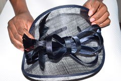 Female hands clutching a blue fancy hat. Female preparing for church Royalty Free Stock Photos