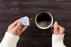 Female hands with coffee and heart shaped cookies on wooden table, top view.  stock photo