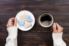 Female hands with coffee and heart shaped cookies on wooden table, top view.  royalty free stock image