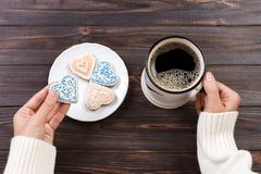 Female hands with coffee and heart shaped cookies on wooden table, top view.  stock photos