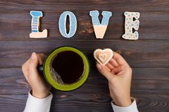 Female hands with coffee and heart shaped cookies on wooden table, top view. Love concept.  stock images