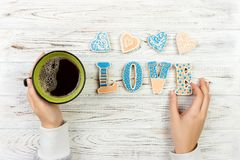Female hands with coffee and heart shaped cookies on wooden table, top view. Love concept. Cookies love letter.  royalty free stock images