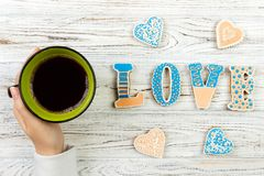 Female hands with coffee and heart shaped cookies on wooden table, top view. Love concept.  royalty free stock images