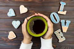 Female hands with coffee and heart shaped cookies on wooden table, top view. Love concept.  royalty free stock photography