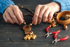 Female hands with colored beads necklace manufacturing Stock Photos