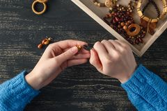 Female hands with colored beads necklace manufacturing Royalty Free Stock Photography