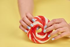Female hands with colorful lollipop. Woman hands with manicure holding tasty bright lollypop on yellow background Royalty Free Stock Photo
