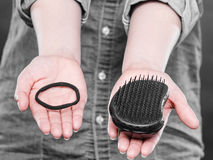 Female hands with comb and elastic hair. Stock Photography