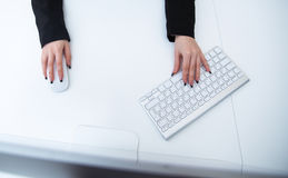 Female hands with computer mouse and keyboard Royalty Free Stock Image