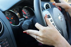 Female hands controlling steering wheel. And driving Stock Photography