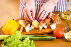 Female hands cooking trout fish in domestic Royalty Free Stock Photo